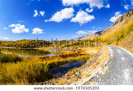 Lake trail among the mountain hills. Paved trail in mountains. Mountain trail view