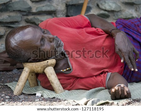 "LAKE TURKANA, KENYA - JANUARY 12:  El molo man resting on traditional ""head rest"". January 2013 at Lake Turkana"