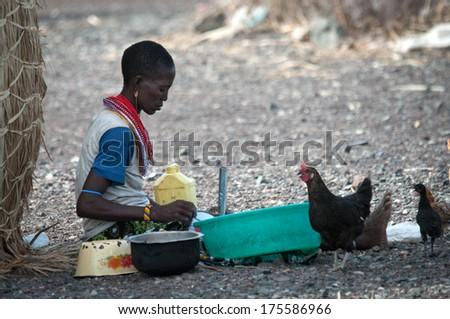 LAKE TURKANA, KENYA-JANUARY 12: Unidentified El molo woman makes rural work January 12, 2013 near lake Turkana, Kenya. The El molo are one of the disappearing tribes of Africa