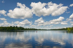 Lake view from a cottage dock in Algonquin Park, Ontario. Clouds are reflecting on the water while a red canoe is crossing the lake. The person canoeing is wearing a life jacket.