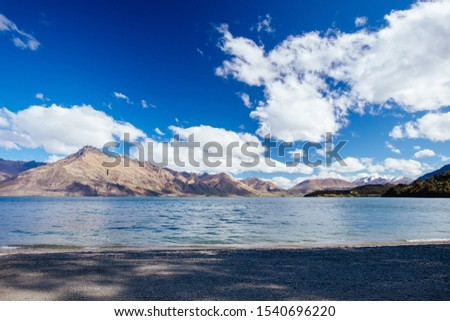 Lake Wakatipu and surrounding mountains, known as Tooth Peaks, on a sunny spring day near Glenorchy in New Zealand #1540696220