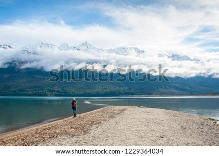 Lake Wakatipu, Glenorchy, New Zealand. Man gazes at the view. Breathtaking landscape, snow capped mountain peaks, long white cloud, still water and  sandy shore #1229364034