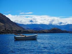 Lake Wanaka - a small row boat floats on Lake Wanaka in Otago, New Zealand's South Island. Mountains and low cloud landscape photograph.