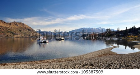 Lake Wanaka and boats with the Southern Alps in the background. Central Otago, New Zealand. In the foreground note how low the lake level is after one of the hottest and driest summers on record.