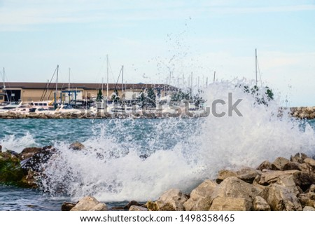 Lake wave crashing against a seawall of boulders near yachts safe in city marina, summer in Kenosha, Wisconsin, USA, with digital oil-painting effect, for themes of proximity, risk, protection #1498358465