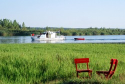 Lake with a cruise ship and tourists. Two red chairs are waiting for falling in love for Valentine's Day, instead of that picnic.  River bank, meadow, green grass and a boat sailing, towing a boat.