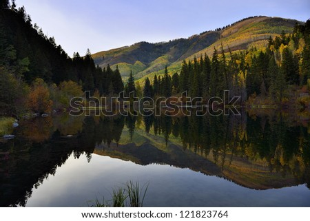 lake with reflection of the mountains and golden, green and red aspen in Colorado during foliage season