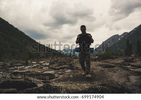 Lake with rocky ridge. Beautiful landscape. The tourist goes over the rocks on the shore of the lake. Altay Russia. - Shutterstock ID 699174904