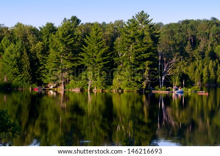 Lake with trees and a boat reflected in the water