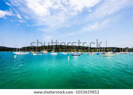 Lakeside Holidays. Great lake Klagenfurt am Wörthersee. The large lake of Klagenfurt in Austria. Many boats are anchored. Summer holiday resort of many European tourists. Crystal blue water. #1053659852