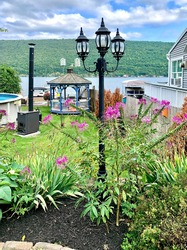 Lakeside house gardening landscape, on Canandaigua Lake - Naples, New York, the fourth longest of the Finger Lakes. Scenic view in summer, with mountain and lake as the background