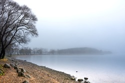 Lakeside shore and islands hidden behind thick fog. Stones on the coast; sand and pebble beach; pines silhouettes. Early morning; misty landscape.