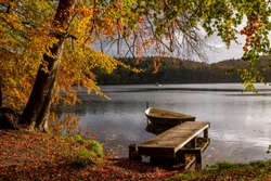 lakeside view with jetty and row boat in beautiful fall landscape