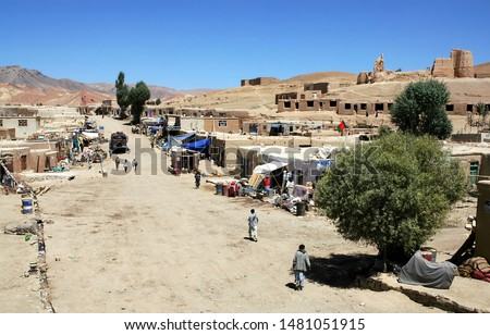 Lal Wa Sarjangal, Ghor Province in Central Afghanistan. This is the dusty main street in Lal. The low basic buildings and dirt road are typical in remote towns in Afghanistan. Note the Afghan flag.