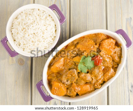 Lamb and sweet potato peanut stew served with white rice. Caribbean and West African dish. Overhead shot.