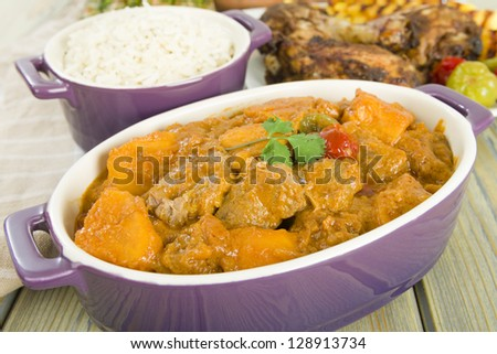 Lamb and sweet potato peanut stew served with white rice. Jerk chicken and grilled pineapple on background. Caribbean and West African traditional dishes.