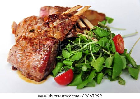 Lamb chops and green salad with baby tomatoes on a plate in a restaurant