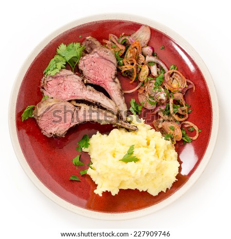Lamb chops cut from a roast lamb rack and served with creamed garlic potato and onion relish