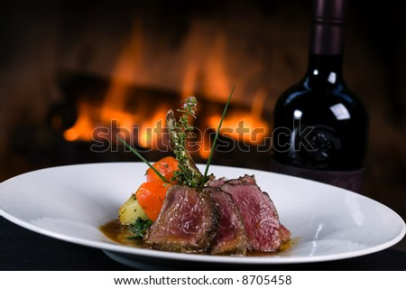 Lamb chops with vegetables and a bottle of wine in front of a fireplace