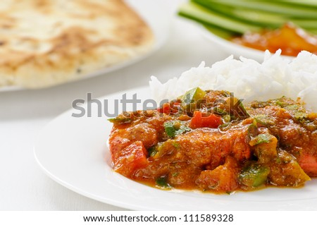 Lamb jalfrezi, a meat curry with red and green peppers, with naan, cucumber and mango chutney behind