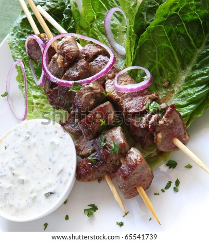 Lamb kebabs with tzatziki cucumber yogurt. On kos lettuce, with red ...