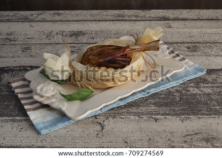 lamb shank cooked in the oven in a parchment paper over rice served on a dark wooden board with white rustic background Stock fotó ©