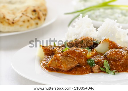 Lamb vindaloo, a spicy meat and potato curry served on rice, garnished with coriander, with naan and raita behind