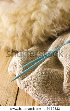 lambs wool, sheep, knitting needles on a wooden board