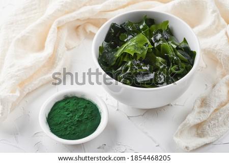 laminaria (Kelp) seaweed and spirulina powder in white bowl background