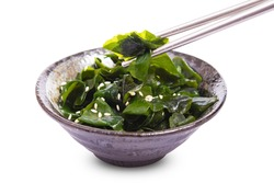 Laminaria (Kelp) seaweed with sesame and chopsticks Isolated on White background. miyeok muchim. korean seaweed salad with clipping path