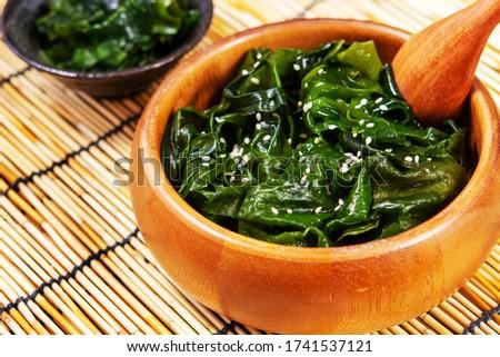 Laminaria (Kelp) Seaweed with sesame in wooden bowl on table background. miyeok muchim. korean Seaweed Salad