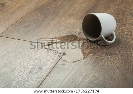 Laminate background.. Wooden laminate and parquet board with spilled water. Moisture protection of a floor Zdjęcia stock ©