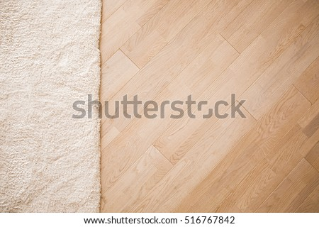 Laminate parquete floor. Light wooden texture. Beige soft carpet. Warm interior design