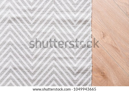 Laminate parquete floor. Light wooden texture. Thin gray and white carpet. Minimalism interior design concept