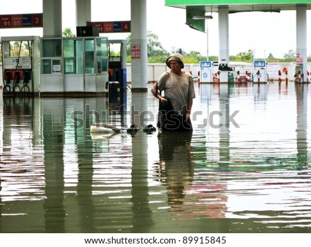 LAMLUKKA (PATHUMTHANI), THAILAND – CIRCA NOVEMBER 2011 – An unidentified man fishes with a net in the floodwater circa November 2011 in Lamlukka.