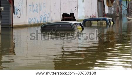 LAMLUKKA (PATHUMTHANI), THAILAND – CIRCA NOVEMBER 2011 – Two flooded cars in the floodwater circa November 2011 in Lamlukka. The entire province has been flooded due to an unprecedented rainy season.
