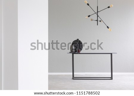 Lamp above black table in grey and white empty room interior with copy space. Real photo