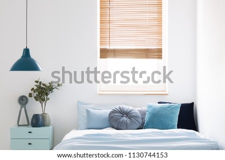 Lamp above blue cabinet with plant next to bed in simple bedroom interior with window. Real photo #1130744153