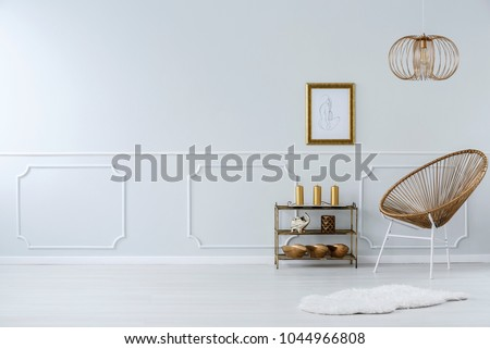 Lamp above gold chair and white fur in sophisticated living room interior with poster and copy space #1044966808