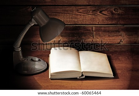 lamp and opened book on wooden table