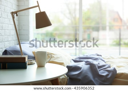 Lamp, books and cup on a side table
