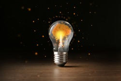 Lamp bulb with shining brain inside on wooden table against black background. Idea generation