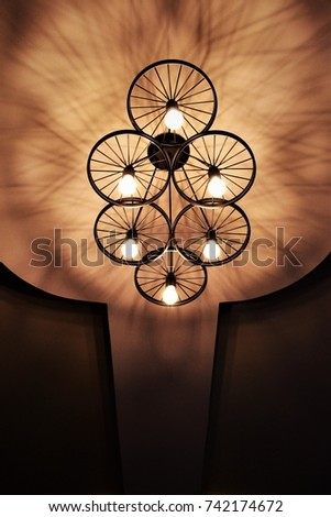 Lamp hanging from the ceiling.Hanging lamp hanging from the ceiling decorated with a wheel. #742174672