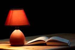 Lamp illuminating a book on wooden table