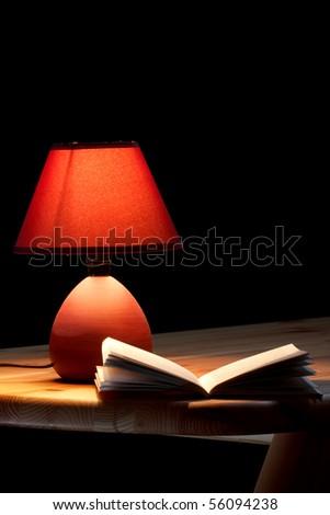 Lamp illuminating a book on wooden table - stock photo