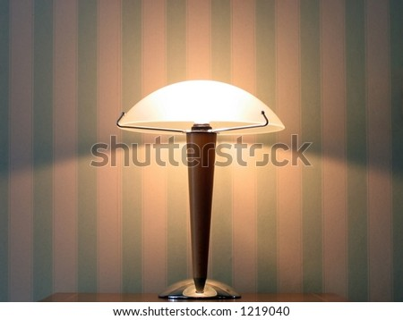 Lamp in front of a wall. Striped wallpaper.