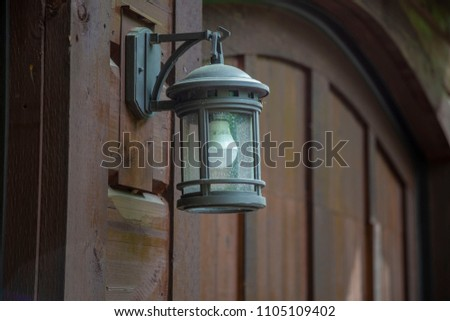 Lamp lantern wood wall garage outside close up light bulb feature on off