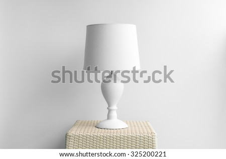 Lamp on a night table next to a bed.