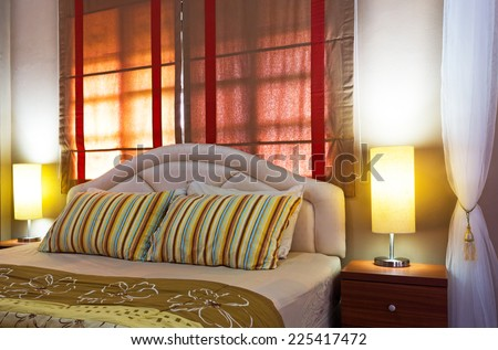 Lamp on a night table next to a bed, cozy living bedroom
