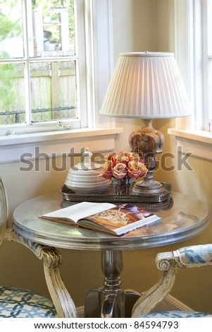 Lamp on a table with flowers and a book near a window in a corner